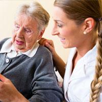 קשישה עם מטפלת מסתכלות יחד על משהו