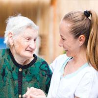 קשישה עם מטפלת מביטות אחת בשניה בחיוך