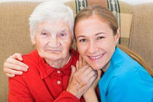 תמנה של קשישה ומטפלת מחייכות אל המצלמה
