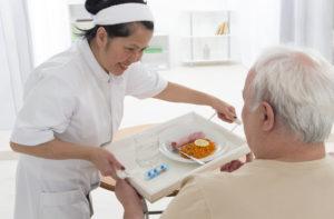 עובדת זרה מגישה מגש אוכל למטופל