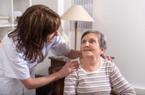 אישה מבוגרת יושבת ומטפלת שמה ידיה על כתפי האישה