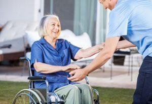 קשישה בכיסא גלגלים עם עזרה של מטפל