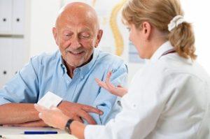 קשיש עם מטפלת שמסבירה לו על התרופות
