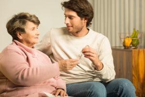 תמונה של קשישה עם בן משפחה יושבים על ספה