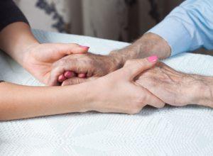 זוג ידיים של אישה צעירה מחזיק זו ידיים של אדם קשיש
