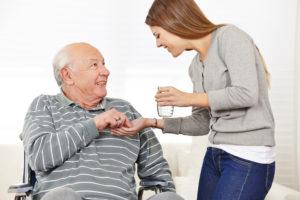 אדם מבוגר עם מטפלת שנותנת לו תרופה