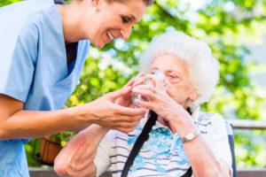 מטפלת שמסייעת לאישה קשישה לשתות כוס מים