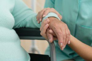 רואים חלק מקשיש שיושב על כיסא גלגלים ואחות מחזיקה את ידו