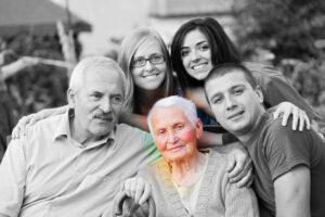 משפחה יושבת על ספספל כשבמרכז קשישה שמוארת באור צבעוני וכל השאר בשחור לבן