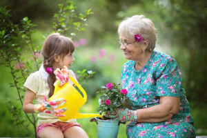סבתא ונחדה יושבות בגינה ומשקות עציצים