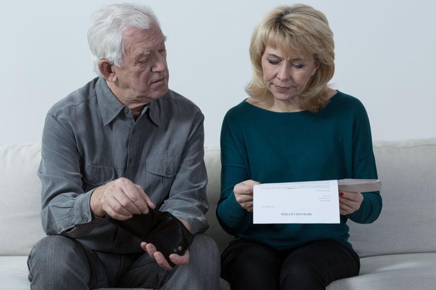 שני מבוגרים יושבים על הספה עם ניירות ביד