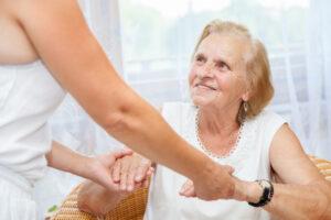 תמונת אווירה של קשישה שמחזיקה ידיים למטפלת (רואים חלקית את המטפלת)